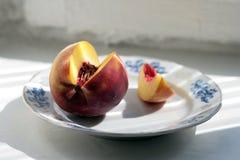 Rijpe Perzik op plaat en zonstralen Royalty-vrije Stock Fotografie