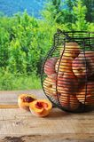 Rijpe perziken in mand Stock Afbeeldingen