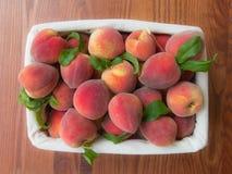 Rijpe perziken in mand Stock Foto
