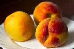 Rijpe perziken op een witte plaat Stock Fotografie