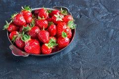 Rijpe rode aardbeien in een plaat op een concrete achtergrond Stock Foto's