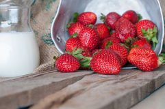 Rijpe rode aardbeien en melk op houten lijst royalty-vrije stock fotografie