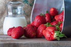 Rijpe rode aardbeien en melk op houten lijst stock fotografie