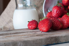 Rijpe rode aardbeien en melk op houten lijst royalty-vrije stock afbeeldingen