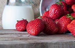 Rijpe rode aardbeien en melk op houten lijst stock foto