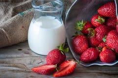 Rijpe rode aardbeien en melk op houten lijst stock afbeelding