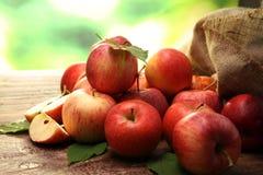 Rijpe rode appelen met bladeren op houten achtergrond Stock Afbeeldingen