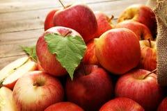 Rijpe rode appelen met bladeren op houten achtergrond Stock Foto