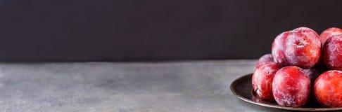 Rijpe Sappige Kleurrijke Rode Organische Pruimen op Uitstekende Metaalplaat Donkere steenachtergrond De ruimte van het exemplaar  Stock Foto