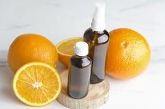 Rijpe sinaasappelen en bruine schoonheidsmiddelenflessen op houten raad Concept oranje olie en schoonheidsmiddelenprocedures royalty-vrije stock foto
