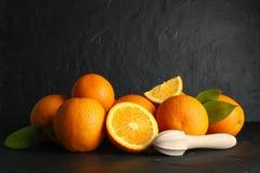 Rijpe sinaasappelen met houten juicer op zwarte lijst tegen donkere achtergrond stock foto's