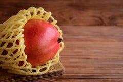 Rijpe smakelijke mango op een bruine houten achtergrond met lege ruimte voor tekst De ruwe sappige foto van het mangofruit royalty-vrije stock foto