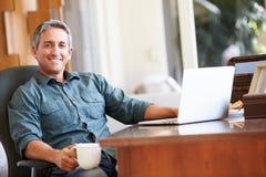 Rijpe Spaanse Mens die Laptop op Bureau thuis met behulp van Royalty-vrije Stock Afbeeldingen