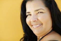 Rijpe Spaanse vrouw die bij camera glimlacht stock afbeeldingen
