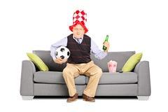 Rijpe sportventilator die een bal en bier het letten op sport houden Stock Foto