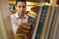 Rijpe student die boek van plank in de bibliotheek selecteren stock afbeelding
