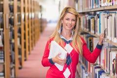 Rijpe student die in de bibliotheek bestuderen Stock Foto