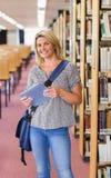 Rijpe student die in de bibliotheek met tablet bestuderen Royalty-vrije Stock Foto's