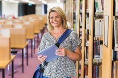 Rijpe student die in de bibliotheek met tablet bestuderen Stock Afbeeldingen
