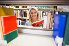 Rijpe student die een boek in bibliotheek lezen Stock Afbeelding