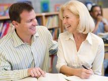 Rijpe student die met privé-leraar in bibliotheek lacht Royalty-vrije Stock Foto's