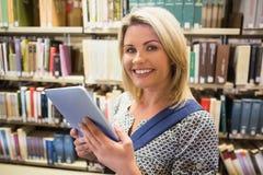 Rijpe student die tablet in bibliotheek gebruiken Stock Afbeelding