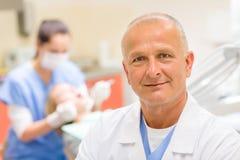 Rijpe tandartschirurg bij bureauportret Stock Foto