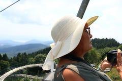 Rijpe toeristenvrouw die een kabelwagen stresa-Mottarone Italië berijden stock afbeelding