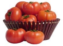 Rijpe tomaten in een mand op een witte achtergrond Royalty-vrije Stock Foto's