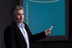 Rijpe trainer die op het scherm met presentatie richten Royalty-vrije Stock Foto's