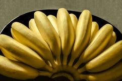 Rijpe unpeeled kleine bananen op zwarte plaat Stock Foto's