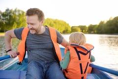 Rijpe vader en weinig zoonsroeien op een rivier of een vijver bij zonnige de zomerdag De tijd van de kwaliteitsfamilie samen op a royalty-vrije stock afbeelding