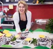 Rijpe verkoopvrouw die in vissenopslag werken royalty-vrije stock fotografie