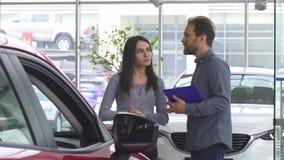 Rijpe verkoper die aan zijn vrouwelijke klant spreken die haar een auto aanbieden stock footage