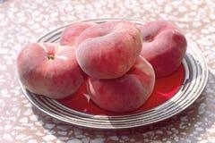 Rijpe vlakke perziken op een plaat Stock Foto