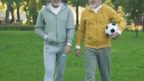Rijpe vrienden met bal die voetbal, sportteam van gepensioneerden, hobby gaan spelen stock video