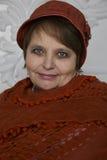 Rijpe vrouw in de winterhoed en gebreide oranje sjaal Stock Fotografie