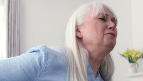 Rijpe vrouw die aan rugpijn lijden stock videobeelden