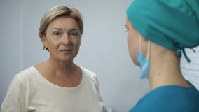 Rijpe vrouw die aan testresultaten luisteren van arts, verdenking van slechte diagnose stock video