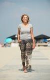 Rijpe vrouw die bij het strand lopen Stock Foto's