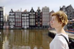 Rijpe vrouw die de beroemde dansende huizen van Amsterdam op zonnige dag bekijken, Nederland royalty-vrije stock afbeeldingen