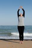 Rijpe vrouw die de zonbegroeting op het strand doen Stock Foto's