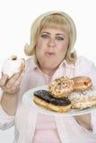 Rijpe Vrouw die Donuts eten Royalty-vrije Stock Fotografie