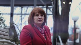 Rijpe vrouw die droevige en nadenkende zitting op een bank kijken Langzame Motie stock video