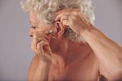 Rijpe vrouw die een gehoorapparaat opneemt in haar oor Stock Foto's