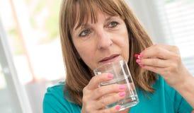 Rijpe vrouw die een geneeskunde nemen tegen hoofdpijn stock foto