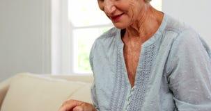 Rijpe vrouw die en een tablet glimlachen gebruiken stock video