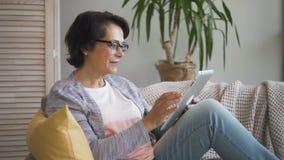Rijpe vrouw die in glazen foto's van haar familie kijken stock footage