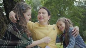 Rijpe vrouw die haar twee leuke kleindochters koesteren die op het gras onder de boom in het park, meisjes zitten die haar kussen stock videobeelden