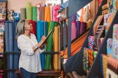Rijpe vrouw die inventaris in haar stoffenwinkel doen royalty-vrije stock foto